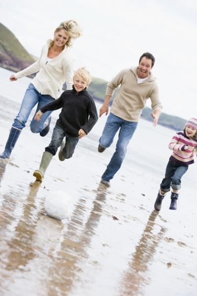 familie spielt fussball am strand laecheln