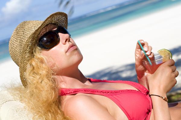 frau entspannt mit drink am strand