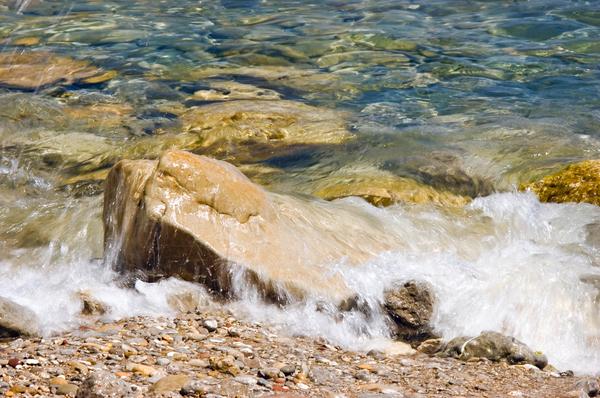 mit wasser ueberspuelter stein am strand