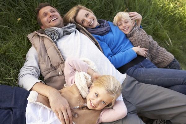 junge familie die zusammen auf gras