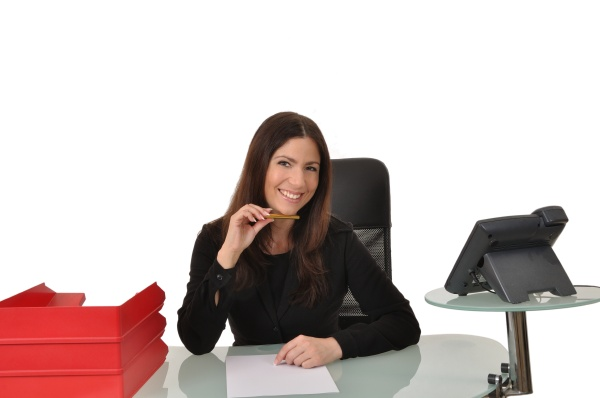 mitarbeiterin sitzt an einem schreibtisch mit