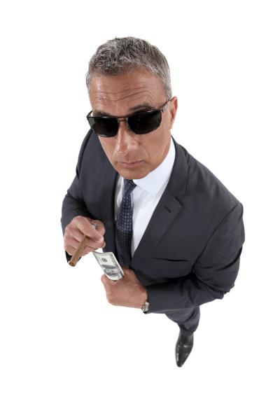 geschaeftsmann der sonnenbrillen mit geld haelt