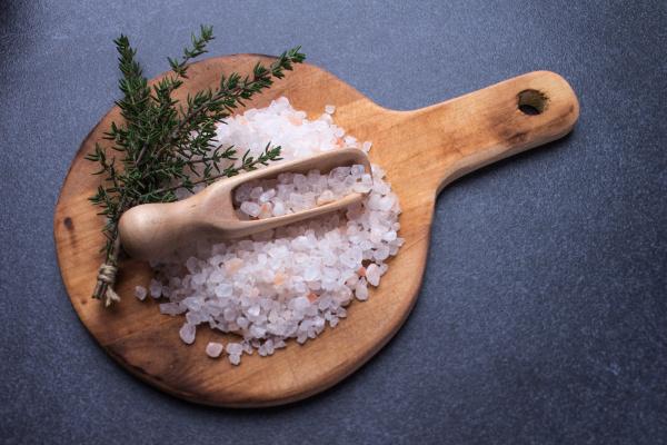 salz mit messloeffel auf rundem holzbrett