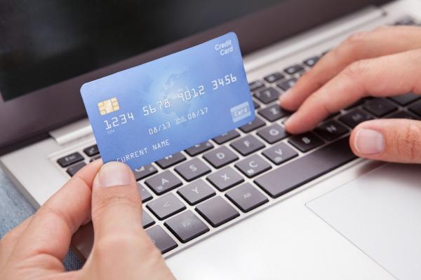 mann sitzt mit laptop und kreditkarte
