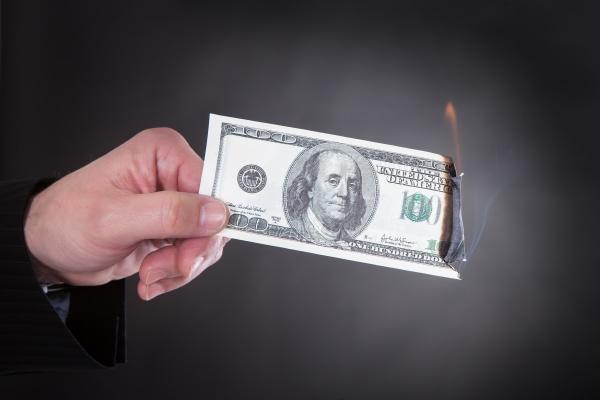 nahaufnahme der hand brennende banknote halten