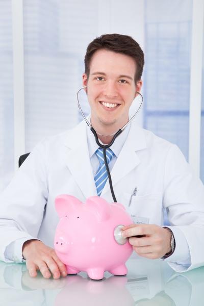 arzt aerztliche untersuchung sparschwein mit stethoskop