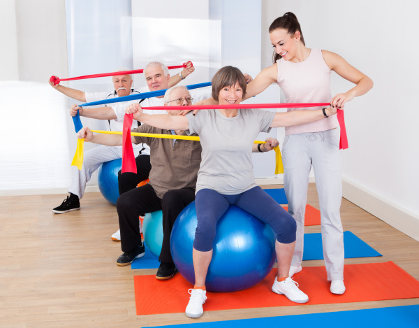 trainer hilft senior leuten im fitnessstudio
