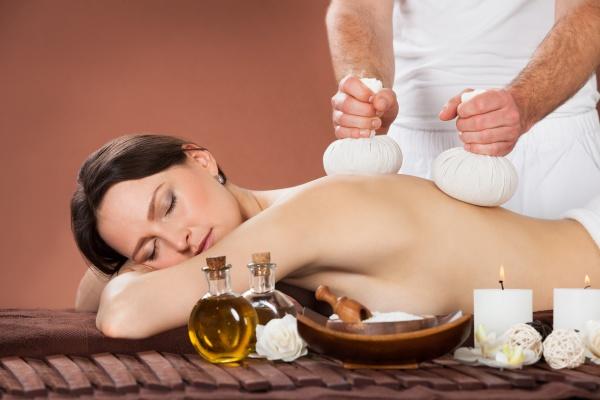 frau empfaengt massage mit kraeuter kompresse