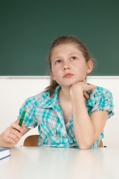 schuelerin sitzt am tisch in schule