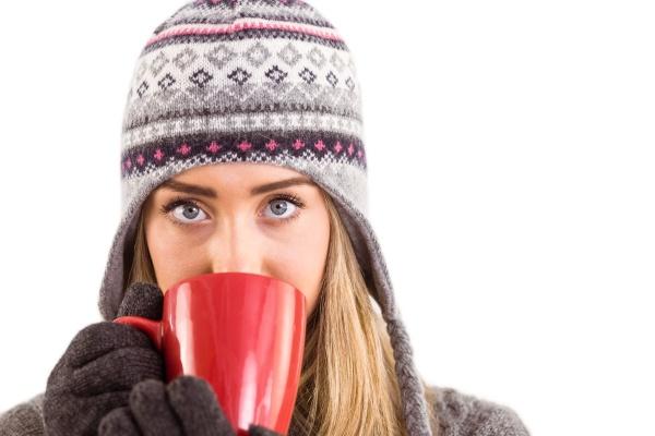 glueckliche blondine in der winterkleidung haelt