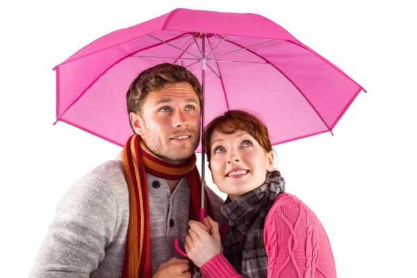 paare die unter einem regenschirm stehen