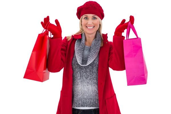 blondine im winter kleidung mit einkaufstueten