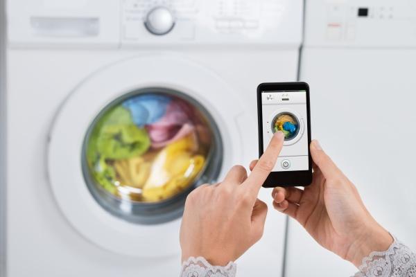 person haende betriebs waschmaschine mit handy