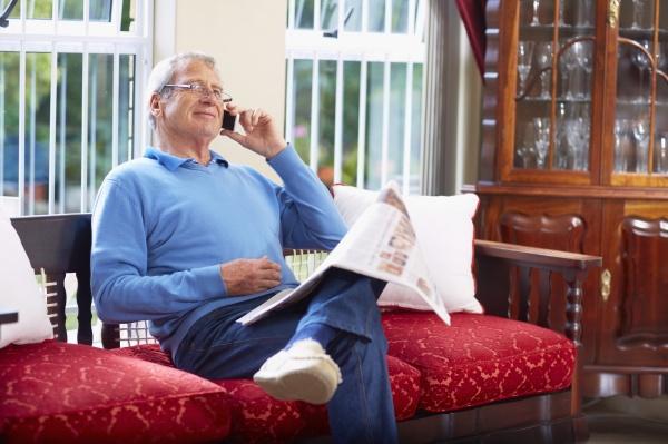 AElterer mann am telefon liest zeitung