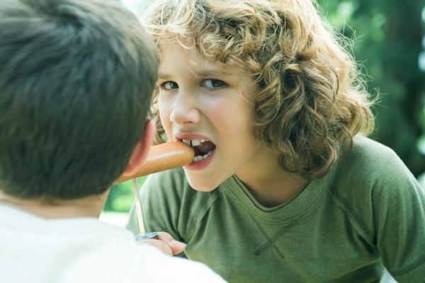 junge isst hotdog aus dem spiel
