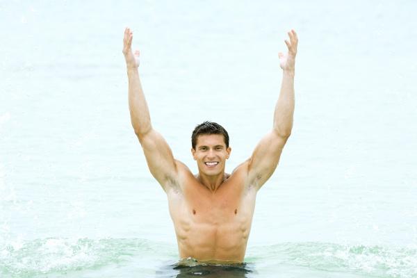 muskuloeser mann steht im schwimmbad mit