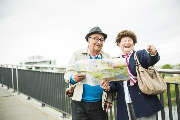 seniorenpaar mit karte auf einer bruecke