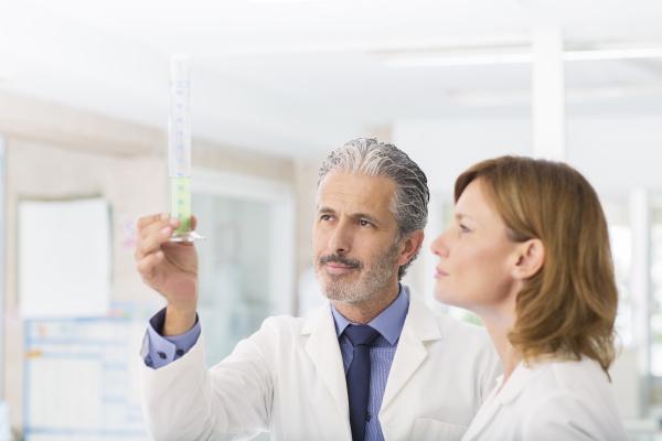 wissenschaftler untersuchen gruene fluessigkeit in rohr