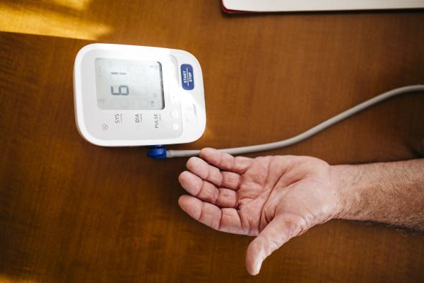 hand des aelteren mannes mit blutdruckmessgeraet