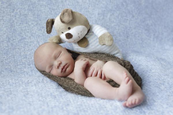 schlafendes neugeborenes und kuscheltier auf einer