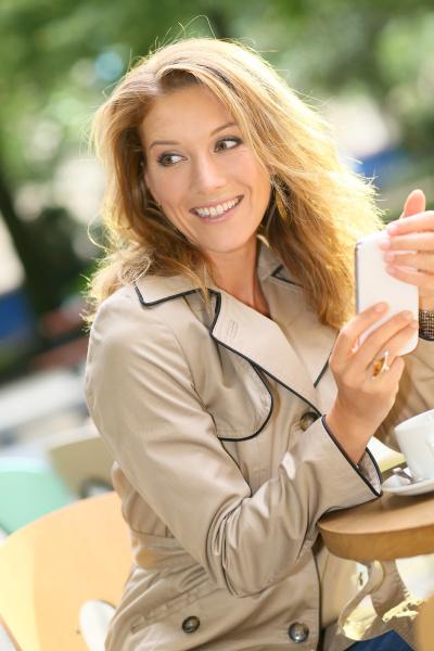 geschaeftsfrau sitzt am kaffeeplatz und benutzt
