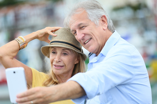 seniorenpaar touristen die sich mit smartphone