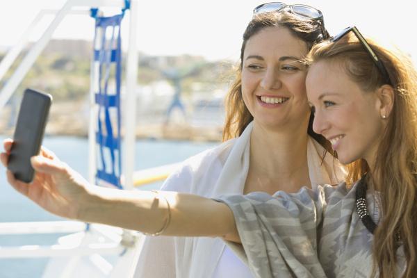 zwei laechelnde frauen nehmen ein selfie