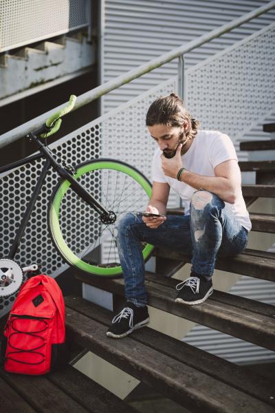 junger mann sitzt auf treppe und