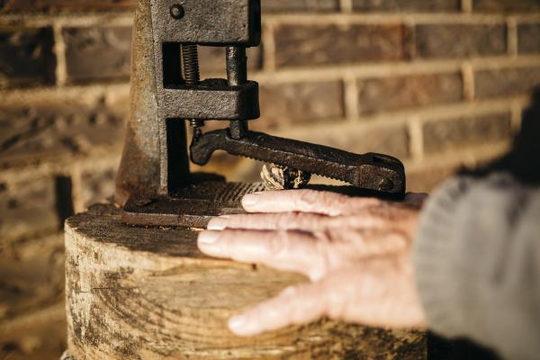 seniorenmensch mit einem alten werkzeug zum