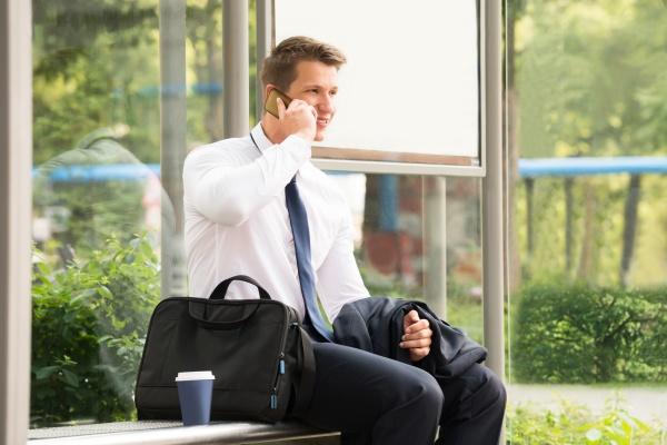 geschaeftsmann gespraech am handy am bushaltestelle