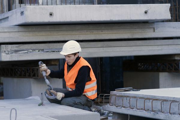 fabrikarbeiter befestigen haken an betonblock in