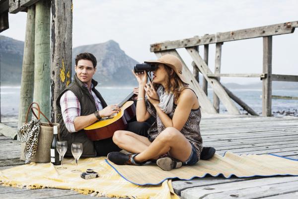 junges paar picnicing auf alten pier