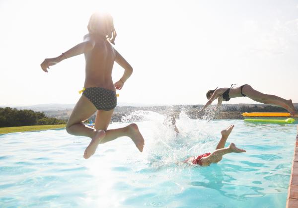 drei leute die in swimmingpool springen