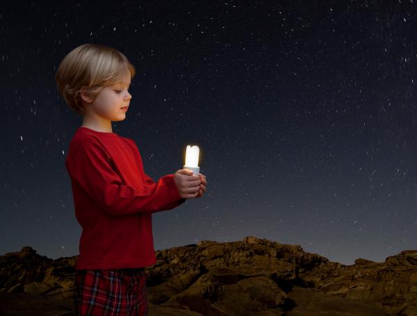 junge mit energiesparlampe
