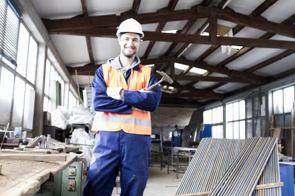 portraet eines fabrikarbeiters mit hammer in