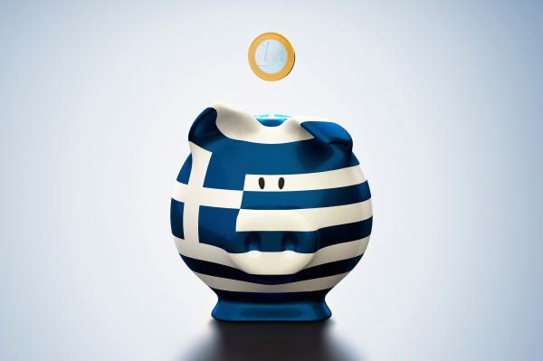 euro muenze ueber griechische flagge sparschwein