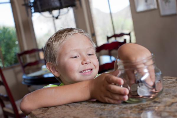 junge setzen ersparnisse in glas