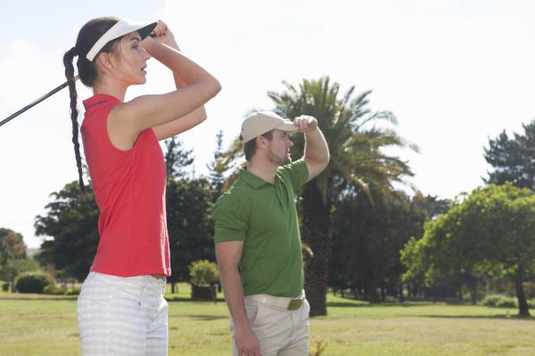 junge frau die golf mit trainer
