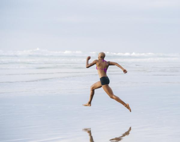 frau im bikini springen am strand