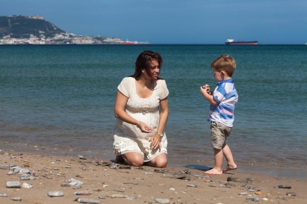 glueckliche schwangere frau spielt mit kind