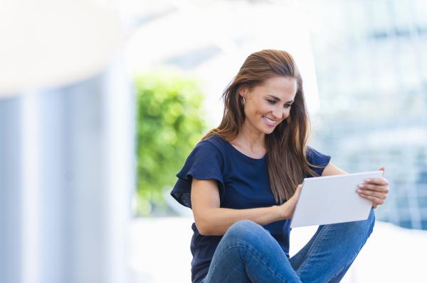 laechelnde bruenette frau mit digitalem tablet