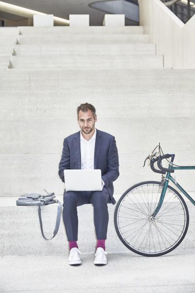 businesssman auf treppen mit laptop neben