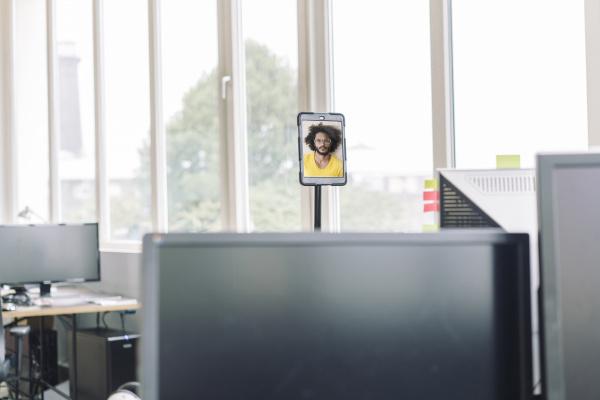 videokonferenz im leeren bueroraum mit computern