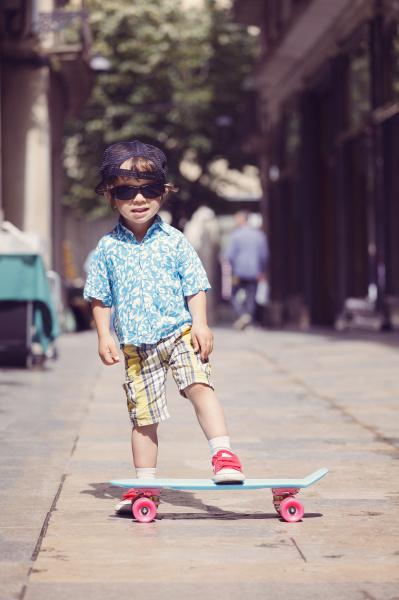 portraet eines kleinen jungen mit skateboard