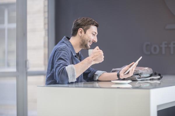laechelnder mann mit digitalen tablet am