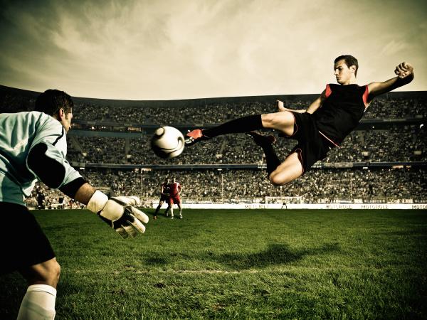 fussballspieler trifft ball am tor