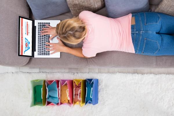 frau auf sofa liegend mit laptop