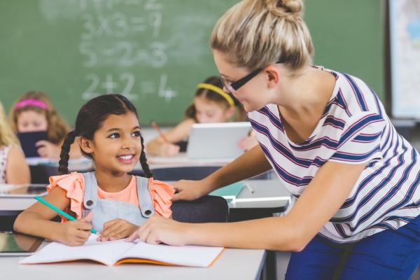lehrer hilft kindern mit ihren hausaufgaben