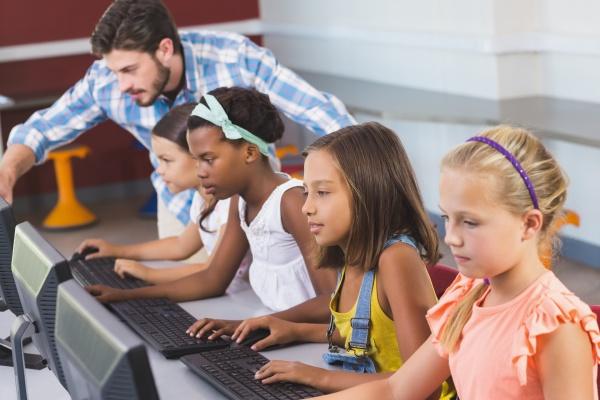 lehrer hilft schuelerinnen beim computerlernen