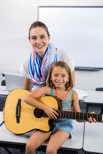 portraet der lehrerin hilft maedchen gitarre